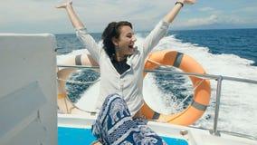 Ο νέος όμορφος θηλυκός ταξιδιώτης στον περιστασιακό ιματισμό έχει την κρουαζιέρα σε ένα γιοτ στην ανοικτή θάλασσα Η ευτυχής γυναί φιλμ μικρού μήκους