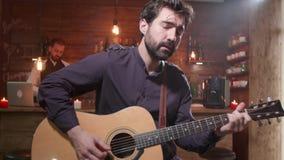 Ο νέος όμορφος κιθαρίστας εκτελεί ένα τραγούδι σε έναν φραγμό απόθεμα βίντεο