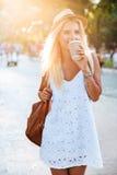 Ο νέος όμορφος ξανθός καφές κατανάλωσης κοριτσιών από παίρνει μαζί το φλυτζάνι Στοκ φωτογραφία με δικαίωμα ελεύθερης χρήσης