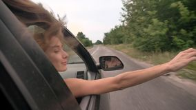 Ο νέος όμορφος ονειροπόλος κοριτσιών βάζει το κεφάλι και διανέμει του παραθύρου αυτοκινήτων κατά τη διάρκεια του γύρου, trevel έν φιλμ μικρού μήκους