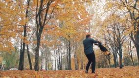 Ο νέος όμορφος πατέρας γυρίζει τη χαριτωμένη μικρή κόρη του γύρω από το κράτημα την παραδίδει το αργό MO πάρκων φθινοπώρου απόθεμα βίντεο
