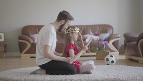Ο νέος όμορφος πατέρας πορτρέτου έντυσε κεφάλι της χαριτωμένης μικρής το μακρυμάλλες κόρης του με την κορώνα και είναι ευτυχής απόθεμα βίντεο