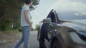 Ο νέος όμορφος τύπος βοηθά τη φίλη του για να βγεί από το αυτοκίνητο απόθεμα βίντεο