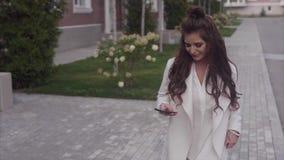 Ο νέος laughting περίπατος γυναικών στην οδό κρατά ένα smartphone Έννοια των καλών ειδήσεων απόθεμα βίντεο
