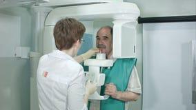 Ο νέος peparing ασθενής οδοντιάτρων γυναικών για αναλύει μια οδοντική πανοραμική των ακτίνων X ταινία στην κλινική απόθεμα βίντεο