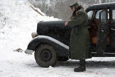 Ο ναζιστικός ανώτερος υπάλληλος στέκεται κοντά στο αναδρομικό αυτοκίνητο Στοκ εικόνες με δικαίωμα ελεύθερης χρήσης