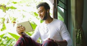 Ο νεαρός άνδρας ακούει τη μουσική στον υπολογιστή ταμπλετών με τα ακουστικά τραγουδά στη συνεδρίαση μιας στη στρωματοειδή φλέβα π απόθεμα βίντεο