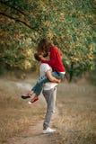 Ο νεαρός άνδρας ανύψωσε επάνω το κορίτσι στα χέρια του και φιλούν στον περίπατο στο φ Στοκ εικόνα με δικαίωμα ελεύθερης χρήσης