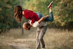 Ο νεαρός άνδρας ανύψωσε επάνω το κορίτσι στην πλάτη του και την φέρνει Στοκ Φωτογραφία