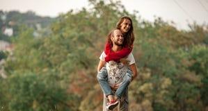 Ο νεαρός άνδρας ανύψωσε επάνω το κορίτσι στην πλάτη του και την φέρνει Στοκ Φωτογραφίες