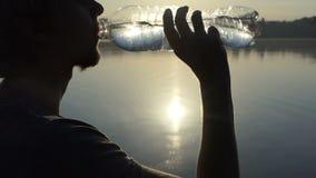 Ο νεαρός άνδρας αυξάνει ένα πλαστικό μπουκάλι πίνει το νερό στο ηλιοβασίλεμα στην slo-Mo απόθεμα βίντεο