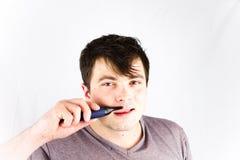 Ο νεαρός άνδρας αφαιρεί την τρίχα από τη μύτη του με trimmer Ο όμορφος νεαρός άνδρας αφαιρεί την τρίχα μύτης με την ηλεκτρική ξυρ Στοκ εικόνες με δικαίωμα ελεύθερης χρήσης
