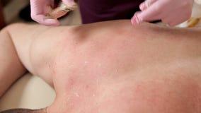 Ο νεαρός άνδρας αφαιρεί την τρίχα στο πίσω μέρος του κεφαλιού του σε ένα σαλόνι ομορφιάς epilation απόθεμα βίντεο