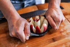 Ο νεαρός άνδρας αφαιρεί τον πυρήνα ενός μήλου χρησιμοποιώντας ένα εργαλείο corer μήλων στοκ φωτογραφία