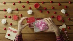 Ο νεαρός άνδρας βάζει την πιστωτική κάρτα στο κιβώτιο δώρων όπως παρούσα, τοπ άποψη φιλμ μικρού μήκους