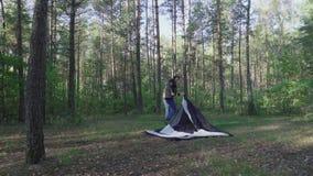 Ο νεαρός άνδρας βάζει τη σκηνή κάλυψης στην αυγή στο δάσος στο πρωί Ο ψαράς τουριστών με μακρυμάλλη κάνει το στρατόπεδο μεταξύ απόθεμα βίντεο