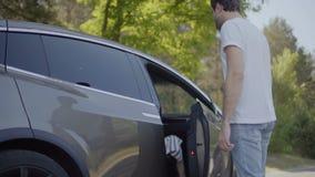 Ο νεαρός άνδρας βοηθά τη φίλη του για να βγεί από το αυτοκίνητο απόθεμα βίντεο