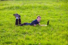 Ο νεαρός άνδρας βρίσκεται στην πράσινη χλόη με το lap-top και την εργασία Στοκ φωτογραφία με δικαίωμα ελεύθερης χρήσης