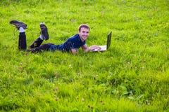Ο νεαρός άνδρας βρίσκεται στην πράσινη χλόη με το lap-top και την εργασία Στοκ εικόνες με δικαίωμα ελεύθερης χρήσης