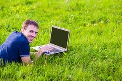 Ο νεαρός άνδρας βρίσκεται στην πράσινη χλόη με το lap-top και την εργασία Στοκ Εικόνα