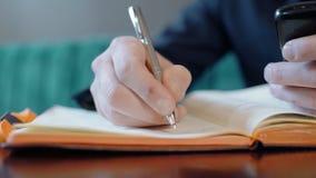 Ο νεαρός άνδρας γράφει στο ημερολόγιο, καθμένος στον πίνακα στον καφέ στο εσωτερικό απόθεμα βίντεο