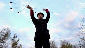 Ο νεαρός άνδρας γυρίζει δύο ανεμιστήρες μετάλλων με τη φλόγα γύρω από τον στην slo-Mo Είναι μαγικό απόθεμα βίντεο