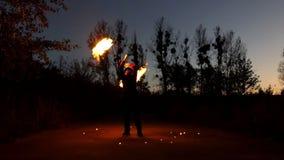 Ο νεαρός άνδρας γυρίζει δύο LIT Flambeaux γύρω Φαίνονται μαγικοί τη νύχτα στην slo-Mo απόθεμα βίντεο