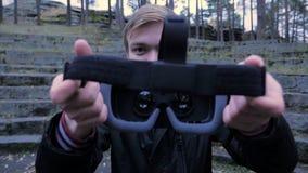 Ο νεαρός άνδρας δίνει μια κάσκα εικονικής πραγματικότητας στο πάρκο Ο νεαρός άνδρας δίνει μια κάσκα εικονικής πραγματικότητας στο Στοκ φωτογραφία με δικαίωμα ελεύθερης χρήσης