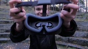 Ο νεαρός άνδρας δίνει μια κάσκα εικονικής πραγματικότητας στο πάρκο Ο νεαρός άνδρας δίνει μια κάσκα εικονικής πραγματικότητας στο Στοκ φωτογραφίες με δικαίωμα ελεύθερης χρήσης