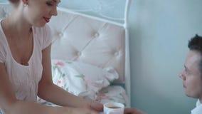 Ο νεαρός άνδρας δίνει στο κορίτσι ένα φλιτζάνι του καφέ το πρωί, χαμόγελο, κινηματογράφηση σε πρώτο πλάνο, σε αργή κίνηση φιλμ μικρού μήκους