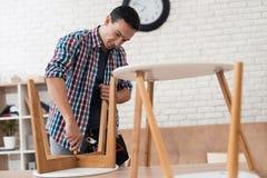 Ο νεαρός άνδρας δοκιμάζεται για να διπλώσει το τραπεζάκι σαλονιού και τα σκαμνιά του Στοκ Εικόνες