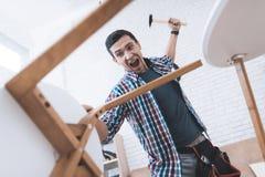 Ο νεαρός άνδρας δοκιμάζεται για να διπλώσει το τραπεζάκι σαλονιού και τα σκαμνιά του Στοκ Φωτογραφία