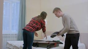 Ο νεαρός άνδρας είναι 0, ενώ αυτός και η φίλη του που συσκευάζουν μια βαλίτσα για ένα ταξίδι Στοκ Εικόνα