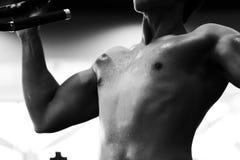 ο νεαρός άνδρας εκτελεί την άσκηση με τη μηχανή στο κέντρο ικανότητας αρσενικό Στοκ εικόνα με δικαίωμα ελεύθερης χρήσης
