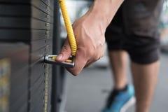 ο νεαρός άνδρας εκτελεί την άσκηση με το τράβηγμα κάτω από τη μηχανή στη CEN ικανότητας Στοκ Φωτογραφίες