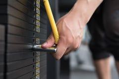 ο νεαρός άνδρας εκτελεί την άσκηση με το τράβηγμα κάτω από τη μηχανή στη CEN ικανότητας Στοκ εικόνα με δικαίωμα ελεύθερης χρήσης