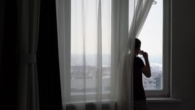 Ο νεαρός άνδρας εξετάζει έξω το παράθυρο την πόλη και πίνει το τσάι απόθεμα βίντεο