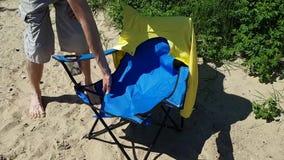 Ο νεαρός άνδρας εξετάζει τη σχισμένη καρέκλα παραλιών Θραύση του εξοπλισμού κατά τη διάρκεια διακοπών στη χώρα απόθεμα βίντεο