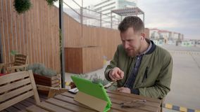 Ο νεαρός άνδρας επικοινωνεί από την κλήση Διαδικτύου μέσω της συνεδρίασης ταμπλετών υπαίθρια απόθεμα βίντεο