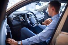 Ο νεαρός άνδρας επιλέγει ένα νέο αυτοκίνητο Η έννοια της αγοράς ενός νέου αυτοκινήτου Στοκ Εικόνες