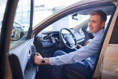 Ο νεαρός άνδρας επιλέγει ένα νέο αυτοκίνητο Η έννοια της αγοράς ενός νέου αυτοκινήτου Στοκ Φωτογραφία
