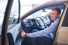 Ο νεαρός άνδρας επιλέγει ένα νέο αυτοκίνητο Η έννοια της αγοράς ενός νέου αυτοκινήτου Στοκ Εικόνα