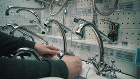 Ο νεαρός άνδρας επιλέγει τη βρύση αναμικτών στο κατάστημα αυτοεξυπηρετήσεων απόθεμα βίντεο