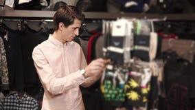 Ο νεαρός άνδρας επιλέγει τις κάλτσες για ένα δώρο σε ένα κατάστημα ιματισμού απόθεμα βίντεο