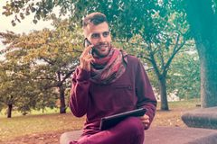 Ο νεαρός άνδρας εργάζεται στον υπολογιστή ταμπλετών μιλώντας στο τηλεφωνικό υπαίθρια δημόσια διάστημα κοντά στο πάρκο στοκ εικόνα