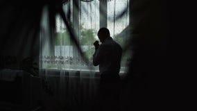 Ο νεαρός άνδρας θαυμάζει την άποψη από το παράθυρο στο σπίτι και έβαλε σε ένα πουκάμισο κίνηση αργή φιλμ μικρού μήκους