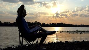 Ο νεαρός άνδρας κάθεται, διαβάζει και γρατσουνίζει τον αυχένα του σε ένα Riverbank στο ηλιοβασίλεμα απόθεμα βίντεο