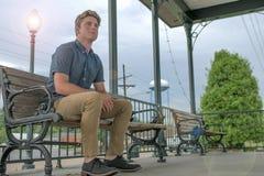 Ο νεαρός άνδρας κάθεται ευτυχώς στον πάγκο πάρκων με έναν ακτινοβολώντας ελαφρύ φωτισμό πόλων επάνω τον ουρανό βραδιού πίσω από τ στοκ εικόνες