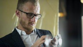 Ο νεαρός άνδρας κάθεται με την κινητή συσκευή στον πίνακα στον καφέ απόθεμα βίντεο