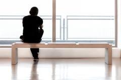 Ο νεαρός άνδρας κάθεται σε ένα γραφείο και προσέχει έξω Στοκ Εικόνα